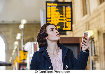 Checking The Departure Board - Young businesswoman is using...