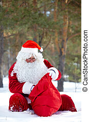 Checking the gifts - Santa Claus looking into his sack in...