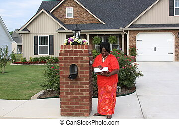 Checking the mail - black female homeowner getting today\'s...