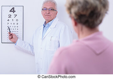Checking the sight - Older ophthalmologist checking his ...