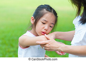 Checking wound - Mother checking wound to her daughter at...