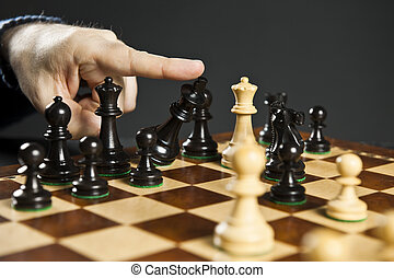 Checkmate in chess - Finger pushing over King chess piece in...