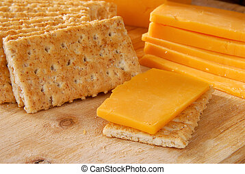 Cheddar cheese and crackers - Sliced cheddar cheese and...