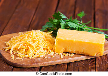 cheddar cheese on board and on a table