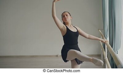 Cheeful adult woman professional ballerina is doing...