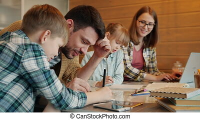 Cheeful guy doing homework with little son talking laughing while woman teaching daughter at home