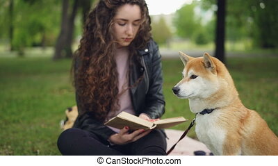 Cheeful student is reading book sitting in the park then...