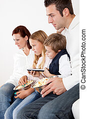 Cheeful young family watching TV at home