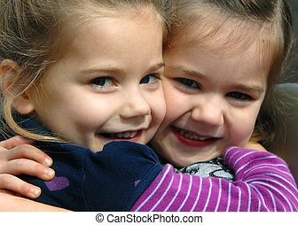 Cheek to cheek - Two sisters hug and squeeze each other. ...
