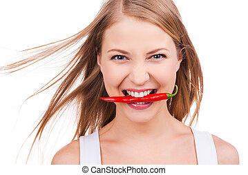 Cheeky as this pepper! Beautiful young woman holding chili pepper in her teeth while standing against white background