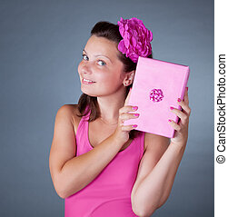 Cheeky beautiful woman with pink gift