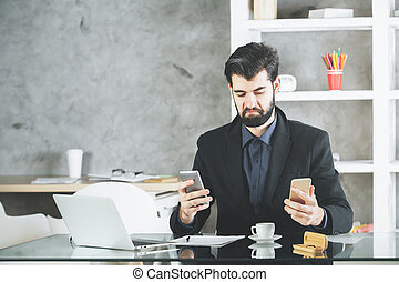 Young businessman with cheeky face expression using two smartphones at workplace with laptop, coffee cup and supplies on glass desktop. Technology concept