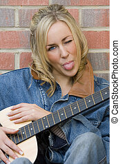 A beautiful young woman leaning on her guitar, winking and sticking out her tongue