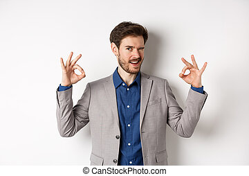Cheeky handsome man in suit winking at you, showing okay signs, all under control gesture, approve good choice, assuring everything OK, standing on white background