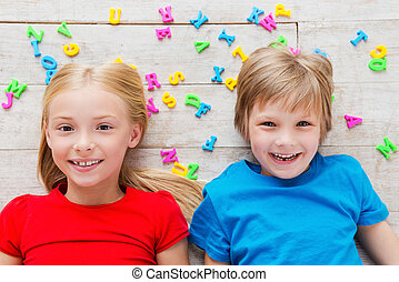 Cheeky kids. Top view of two cute little children looking at camera and smiling while lying on the floor with plastic colorful letters laying around them