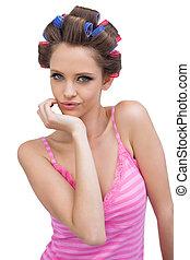 Cheeky model posing wearing hair curlers
