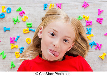 cheeky, pequeno, girl., vista superior, de, cute, menininha, grimacing, enquanto, encontrar-se assoalho, com, plástico, coloridos, letras, deitando, ao redor, dela