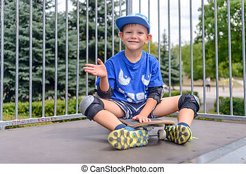 Cheeky young boy sitting on his skateboard
