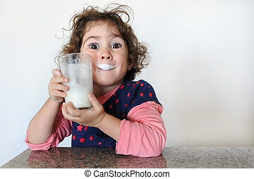 Cheeky young girl drinks milk