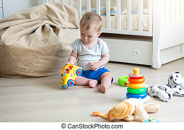 Cheerful 10 months old baby playing on floor with toy car...