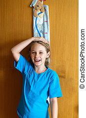 Cheerful 8 years old girl measures the growth on the wooden wall texture background