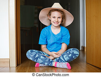 Cheerful 8 years old girl sitting on the floor in her room