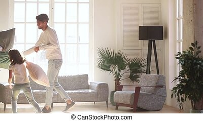 Cheerful active family playing fight with pillows
