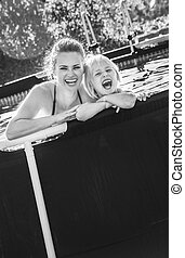 cheerful active mother and daughter in swimming pool