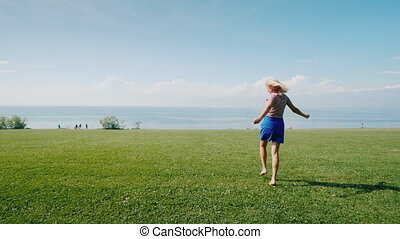 Cheerful active woman is walking on a green meadow. Youth...
