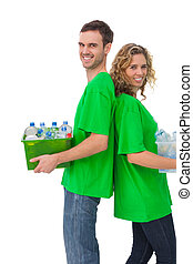 Cheerful activists holding box of recyclables and standing back to back on white background