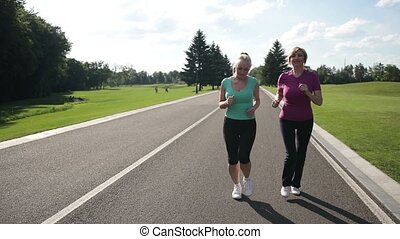 Cheerful adult fit women jogging in the park - Happy...