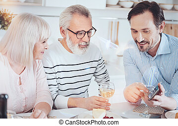 Cheerful adult man showing photos his aged parents