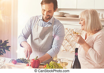 Cheerful adult man standing in the kitchen with his mother