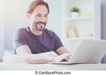 Cheerful adult man workign at home