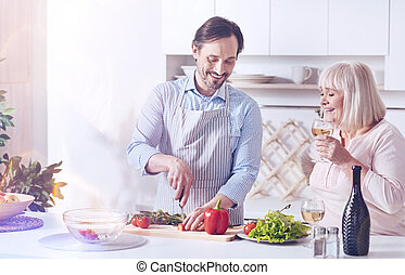 Cheerful adult son helping his mother in the kitchen