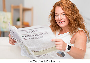 Cheerful adult woman reading newspaper