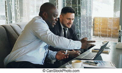 Cheerful African American businessman in formal clothes discussing business project with his caucasian colleague on his laptop in cafe