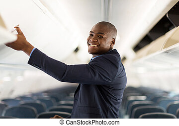 african american businessman opening overhead locker on...
