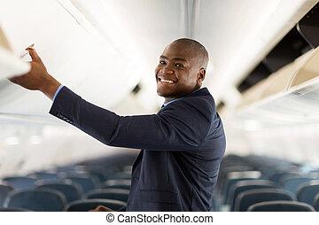 african american businessman opening overhead locker on ...
