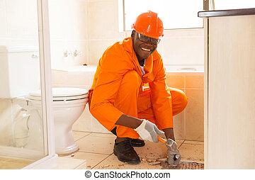 african american construction worker removing floor tiles