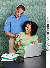 Cheerful African American couple doing home accounts