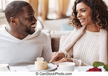 Cheerful African American couple eating the cake in the cafe
