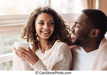 Cheerful African American couple enjoying tea in the cafe