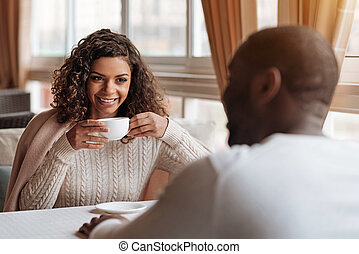 Cheerful African American couple having conversation in the cafe