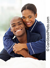 african american couple hugging in bed