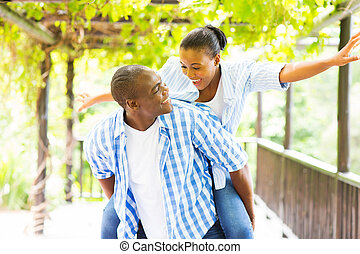 african american couple piggyback - cheerful african...
