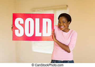 african american girl holding sold sign