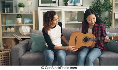Cheerful African-American girl is teaching her Asian friend...