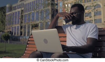 Cheerful African American man drinking coffee while working on laptop