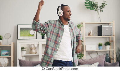Cheerful African American man is dancing and laughing...